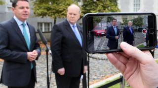 Ministers Michael Noonan (R) and Paschal Donohoe are filmed on an iPhone during a press conference on the Apple Tax ruling, September 2, 2016