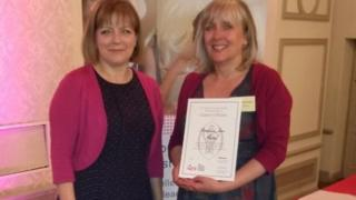 Stephanie Fricker seen on the right with a representative from the Queen's Nursing Institute