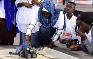 A competitor prepares a robot during the final of the national robotics competition