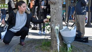 Woman lays a flower at the scene of the attack