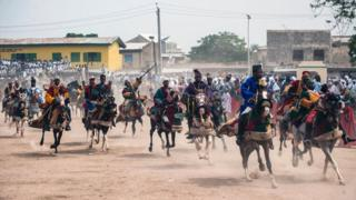 "Members of the Durbar procession race the final stretch to the Emir""s palace in Kano, northern Nigeria on July 6, 2016"
