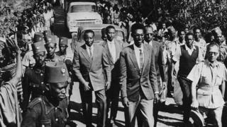 King Kigeli V of Rwanda (front) is flanked by guards and crowds as he is escorted through a town, circa 1959