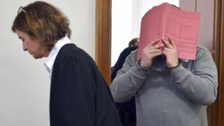 Nurse is led into a court handcuffed hiding behind a folder