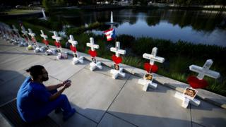 Ernesto Vergne looks at a cross honoring his friend Xavier Emmanuel Serrano Rosado and the other victims at a memorial to those killed in the Pulse nightclub mass shooting a few blocks from the club