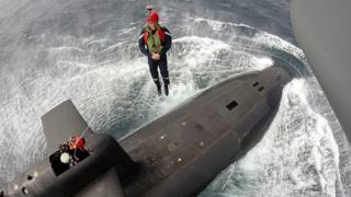 President Macron is lowered down from helicopter aboard the nuclear submarine