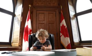 Trudeau junior sits at the prime minister's desk playing with a smartphone, flanked by two Canadian flags