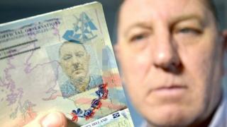 Stuart Boyd holding up passport photo page