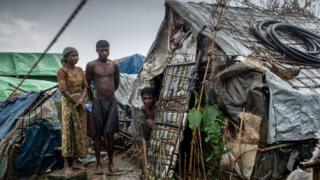 2015년 5월 24일, 한 가족이 미얀마 시트웨 실향민촌의 한 오두막 집에 서있다. 2012년 이후, 많은 로힝야족은 미얀마 라카인주의 실향민촌으로 강제 이주 되었다.