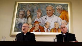 Chilean bishops Luis Fernando Ramos Perez and Juan Ignacio Gonzalez Errazuriz holding a news conference in front of a painting of the Pope