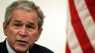Expresidente George W. Bush con una bandera de Estados Unidos.