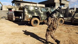 A member of the Libyan National Army (LNA) walks past an armoured vehicle as he holds a position during fighting against jihadists in Qanfudah, on the southern outskirts of Benghazi,
