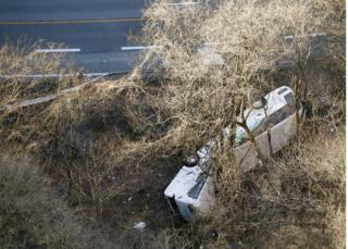 A bus lies after it veered off to the opposite lane on a mountain road in Karuizawa, Nagano prefecture