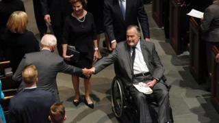 George HW Bush in a wheelchair, grabs someone's hand as he walks down a church aisle at his wife's funeral