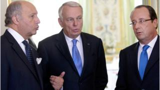 French President Francois Hollande, right, speaks to Laurent Fabius (left), and Jean-Marc Ayrault, in Paris (August 2013)