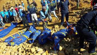 The bodies of miners killed by a landslide are placed on the ground in a jade mining area in Hpakhant, in Myanmar's Kachin state on 22November 2015