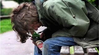 File photo shows a homeless man with a bottle of alcohol