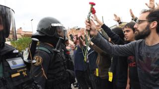 Crowds raise their arms up and a man holds red and pink flowers as police move in on members of the public gathered outside to prevent them from voting in the referendum at a polling station( October 1, 2017)