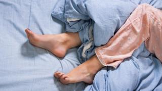 piernas de una mujer en la cama