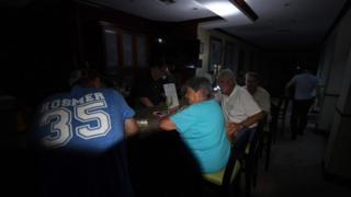 Local residents sit at the bar in the dark after a citywide power failure as Hurricane Harvey hit Corpus Christi, Texas, on August 25, 2017