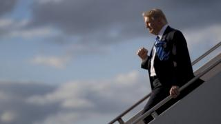 Trump walks down the steps of a plane
