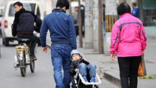 中國一個家庭的父親用拖車帶著孩子