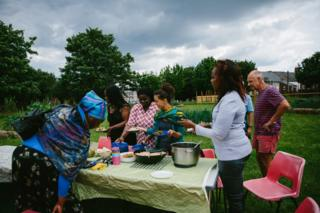 Participants and volunteers share out food on a table outside