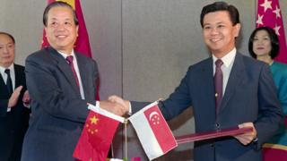 钱其琛(左)与新加坡外长黄根成(右)签署中新建交协议后握手(3/10/1990)