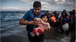 A man holding a baby disembarks from a dinghy after arriving from a Turkish coast to the north-eastern Greek island of Lesbos, Sunday, Oct. 25, 2015.