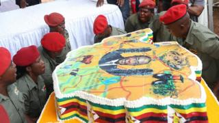 Zimbabweans in red berets struggle to carry in a cake for an event to celebrate President Mugabe's birthday at Matopo Research Centre in Matobo, Matabeleland, Zimbabwe - Saturday 25 February 2017
