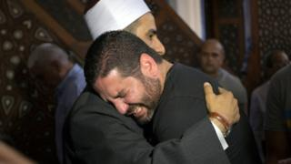 Director Osman Abu Laban, who lost four relatives in a plane crash, is comforted at a mosque
