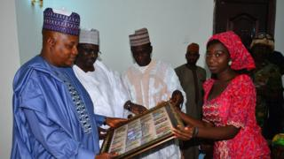 Governor Kashim Shettima receiving a 'thank you' gift from Glory Dama, on behalf of the 21 Chibok schoolgirls freed by Boko Haram in October, 2016.
