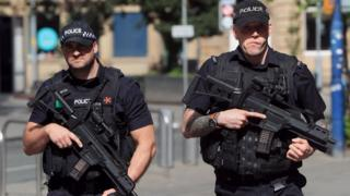Armed police patrol near to the Manchester Arena,