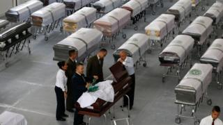 Petugas pemakaman menutup peti mati yang dihias dengan logo Chapecoense, berisi jasad anggota tim di rumah pemakaman San Vicente di Medellin, Kolombia, Jumat, 2 Desember 2016.