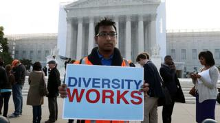 "A man holds a sign that reads, ""Diversity works,"" in front of the US Supreme Court on 10 October 2012."