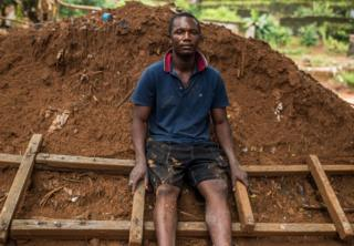 Abdul Mansaray sitting on the ladder that saved him and his family
