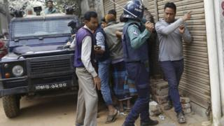 Police try to control crowds that have gathered near an area where suspected Islamist militants are hiding in Dhaka, Bangladesh, 24 December 2016