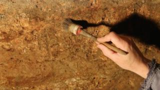 Archaeologist's hand holding a brush against the remains of red paint on the outside Roman wall of the Great Bath
