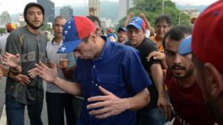 Opposition leader Henrique Capriles reacts to tear gas