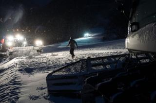 A member of the ski tracks maintenance team attaches the cable of his levelling tractor to the winch of another machine