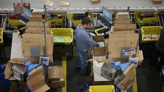 Amazon worker with cardboard boxes