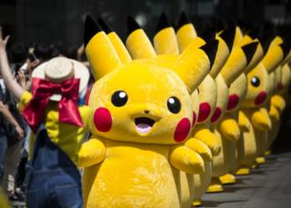 Performers dressed as Pikachu, a character from Pokemon series game titles, march during the Pikachu Outbreak event, 9 August 2017.