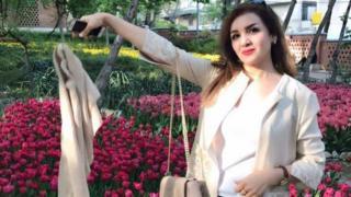 kampanyaya katılan bir kadın beyaz kıyafetiyle poz veriyor.