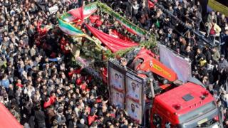 A lorry carrying the coffins of Iranian firemen who were killed in the Plasco building collapse is surrounded by mourners in Tehran (30 January 2017)
