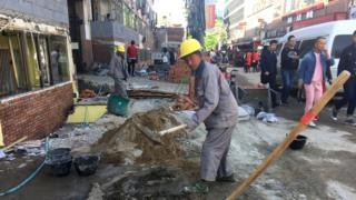 Beijing workers knocking down small shops
