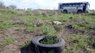 A general view shows a bus (back) at a field as members of the General Prosecutor's Office of the State of Veracruz (unseen) prevented access to the Colinas de Santa Fe in Veracruz, Mexico, 14 March 2017