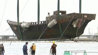 Wooden 'ghost ship' being winched onto the side of a Japanese harbour