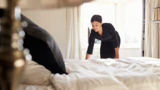 chambermaid makes bed