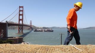 Un obrero con el puente Golden Gate de San Francisco al fondo.