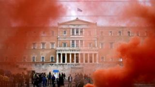 The parliament building is seen through flare smoke during a demonstration of uniformed officers marking a 24-hour general strike against the latest round of austerity in Athens (17 May 2017)