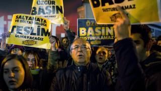 """Cumhuriyet gazetesi önünde protesto, pankartlarda """"saltanata ve diktatörlüğe teslim olmayacağız"""" yazıyor."""